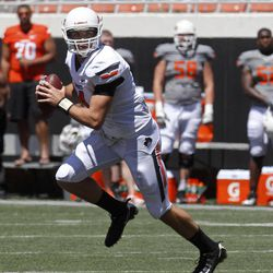 Oklahoma State quarterback J.W. Walsh scrambles during a spring NCAA college football game in Stillwater, Okla., Saturday, April 21, 2012.