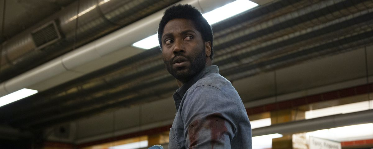 Tenet's John David Washington, bandaged and bloody, looks over his shoulder cautiously in Netflix's Beckett