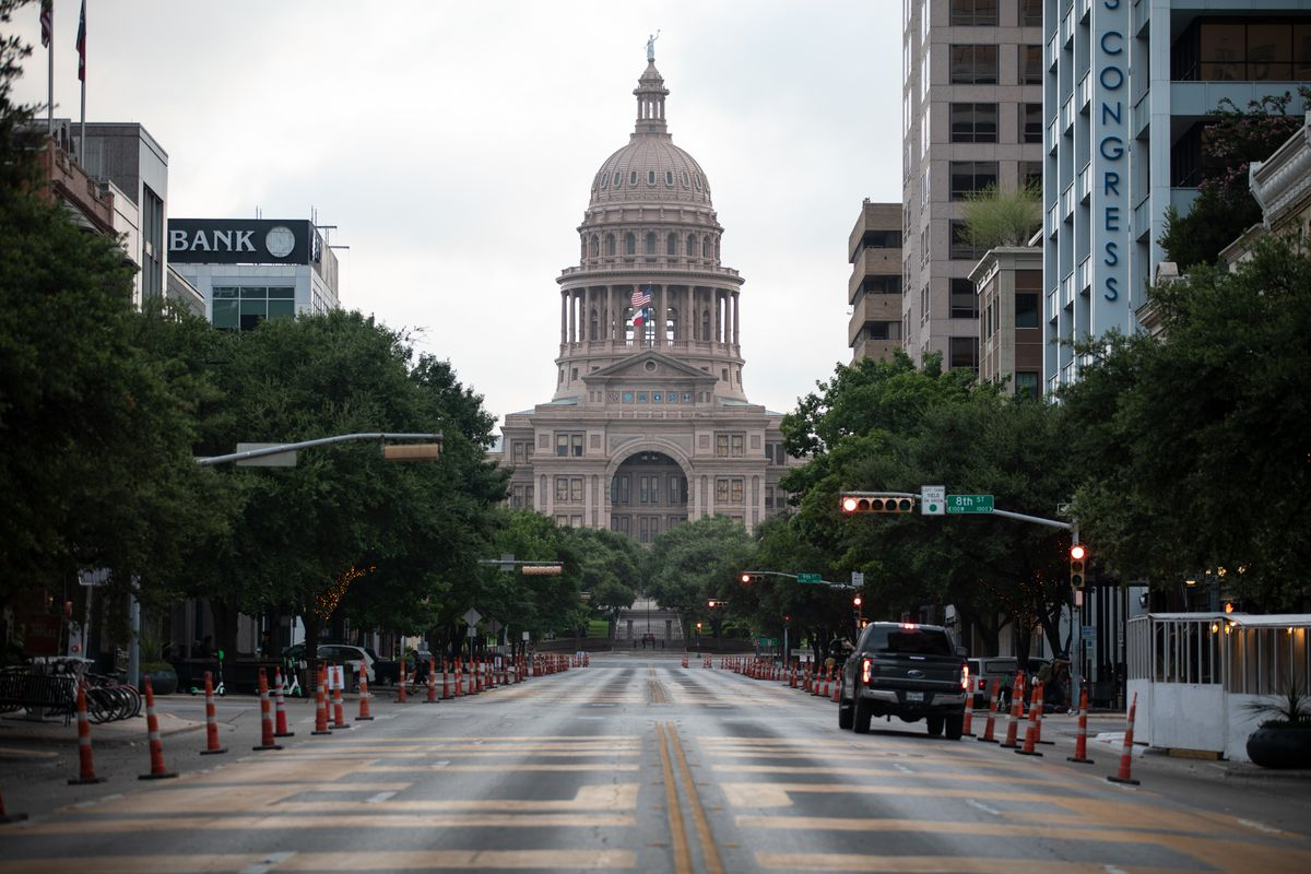 A car drives on Congress Avenue in front of the Texas Capitol building