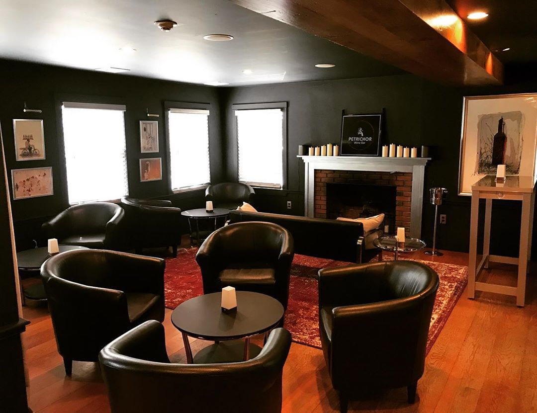 A lounge area with dark brown leather chairs, small round tables adorned with white candles, and a fireplace