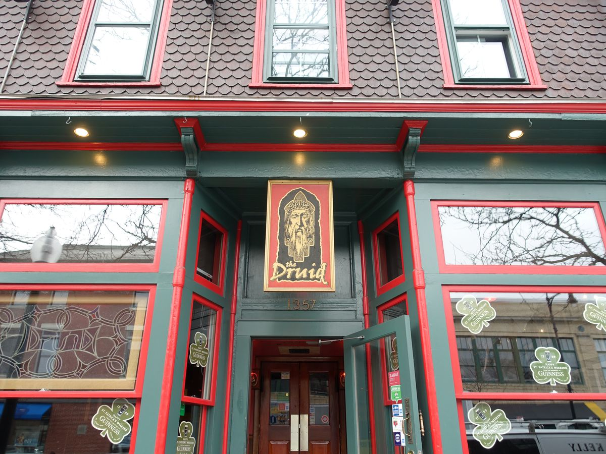 Dark green exterior of a bar with bright red trim and a long vertical sign above the door that says the Druid