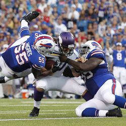 Aug 16, 2013; Orchard Park, NY, USA; Minnesota Vikings quarterback Christian Ponder (7) is sacked by Buffalo Bills defensive tackle Marcell Dareus (99) and defensive end Jerry Hughes (55) during the second quarter at Ralph Wilson Stadium.