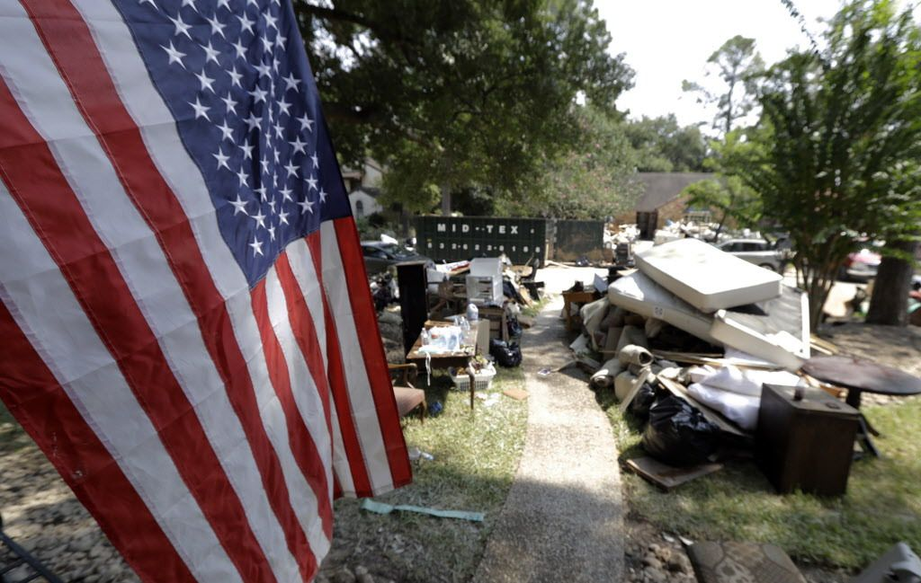 An American flag hangs outside a home damaged by floodwaters in the aftermath of Hurricane Harvey Sunday, Sept. 3, 2017, in Spring, Texas.   David J. Phillip/AP