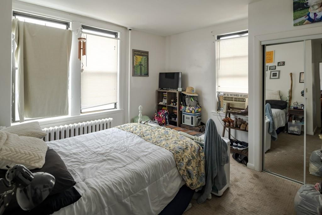 A small bedroom with a bed, a closet with a glass-mirror door, and windows.