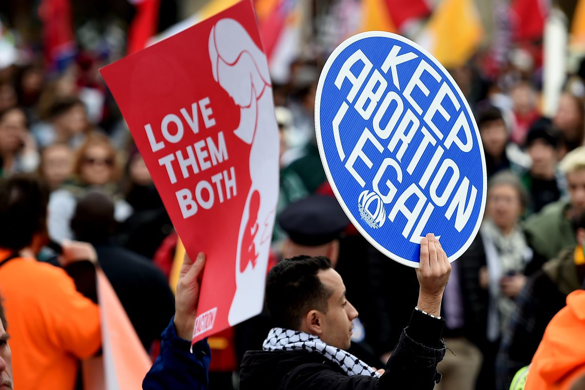 """Activists hold signs, one reading """"love them both"""" and another reading """"keep abortion legal."""""""