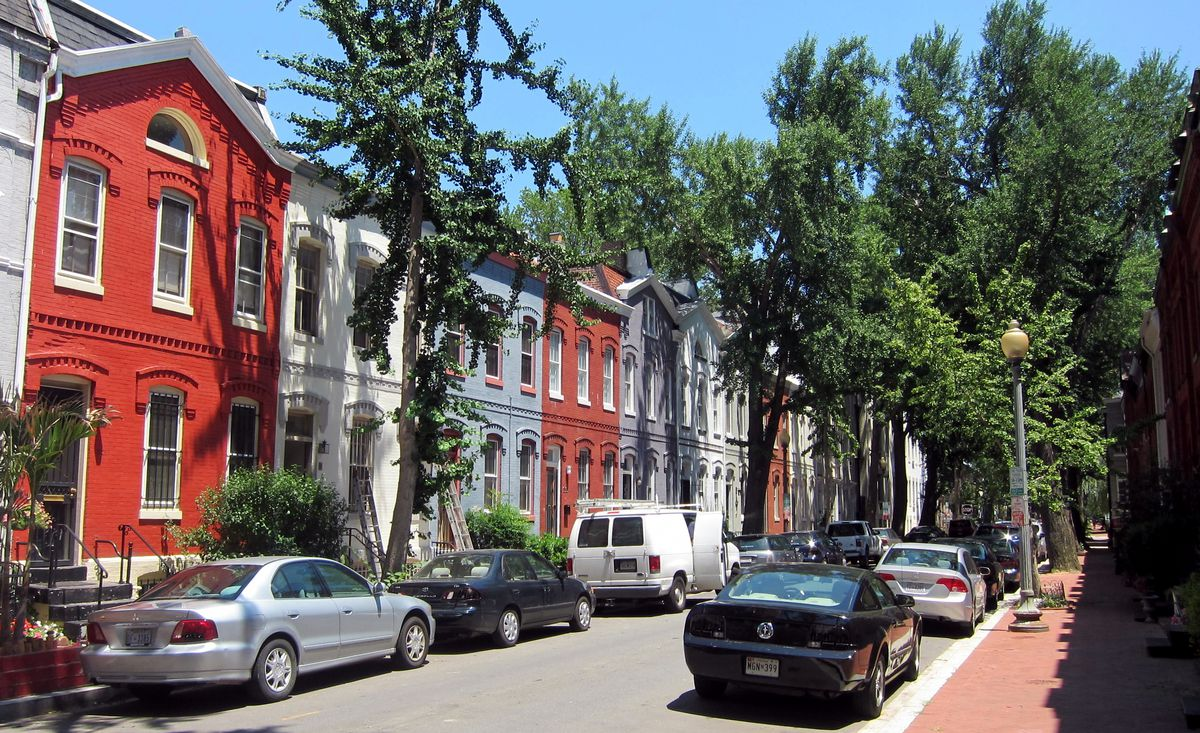Swann Street in Washington D.C. The street is lined with colorful row houses and trees.