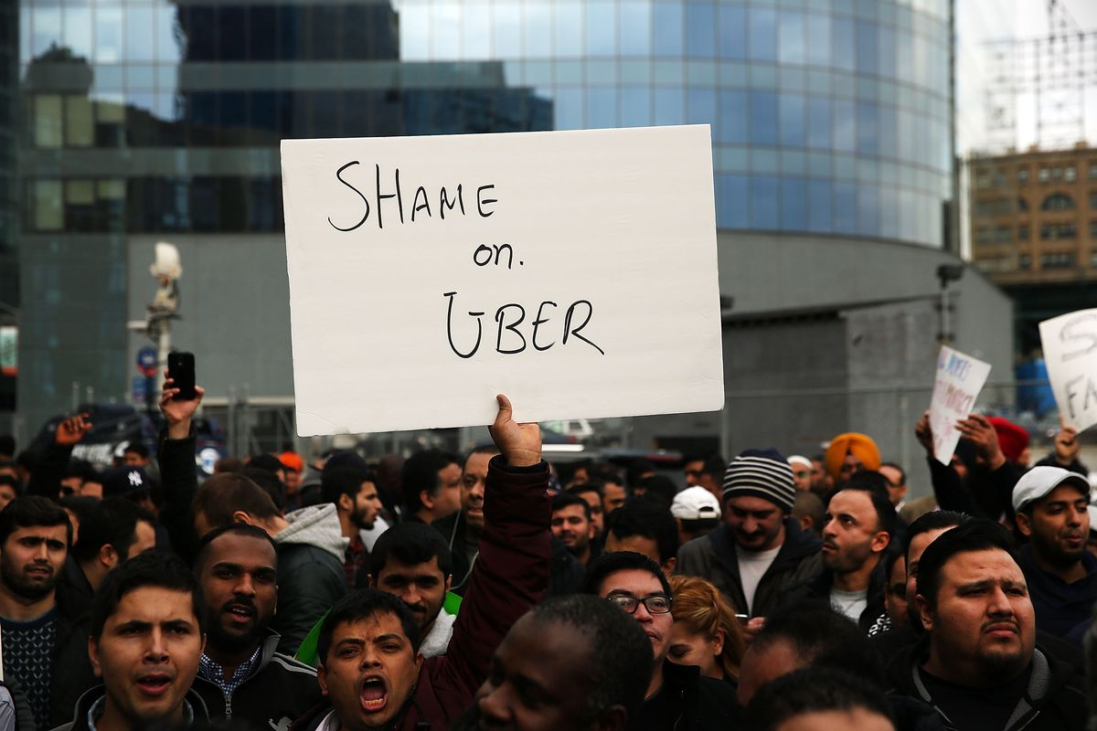 """Crowd with person holding up sign that says """"Shame on Uber"""""""