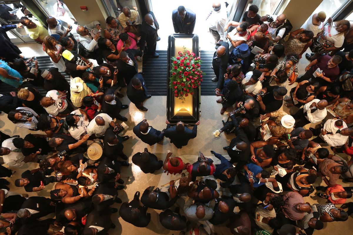 Mourners look on as Michael Brown's casket is removed from the church after his funeral