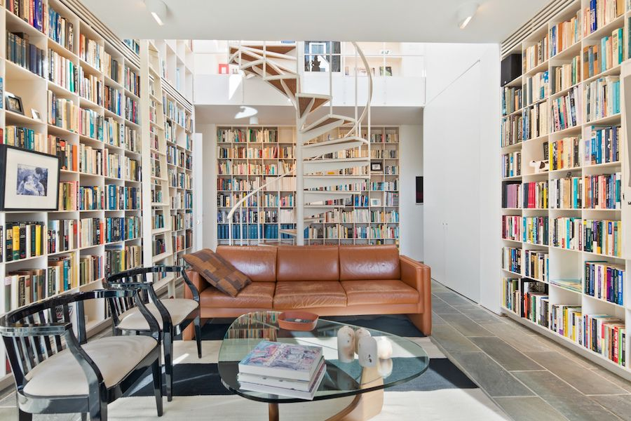A library with built-in bookshelves and a spiral staircase in the middle.