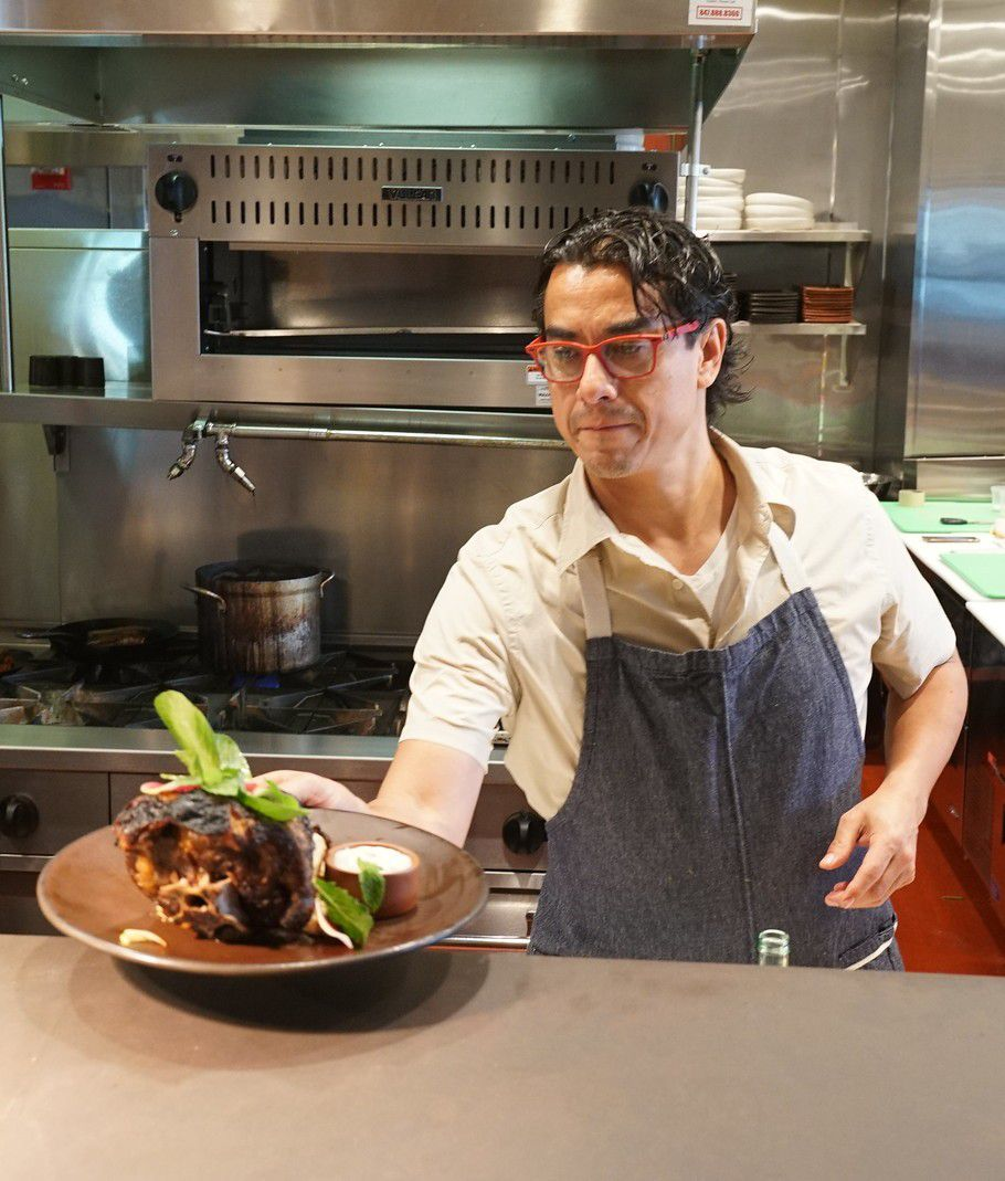 The Mexican chef wears red glasses and a blue apron while placing a pork shank on the pass.