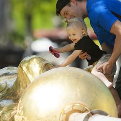 One-year-old Ila Schwab smiles as her father, Tyson Schwab, helps her touch the damaged Angel Moroni statue in Bountiful on Wednesday, June, 1, 2016.