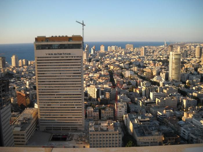 An aerial view of the Shalom Meir Tower in Tel Aviv. The tower is taller than the surrounding city buildings. In the distance is a body of water.