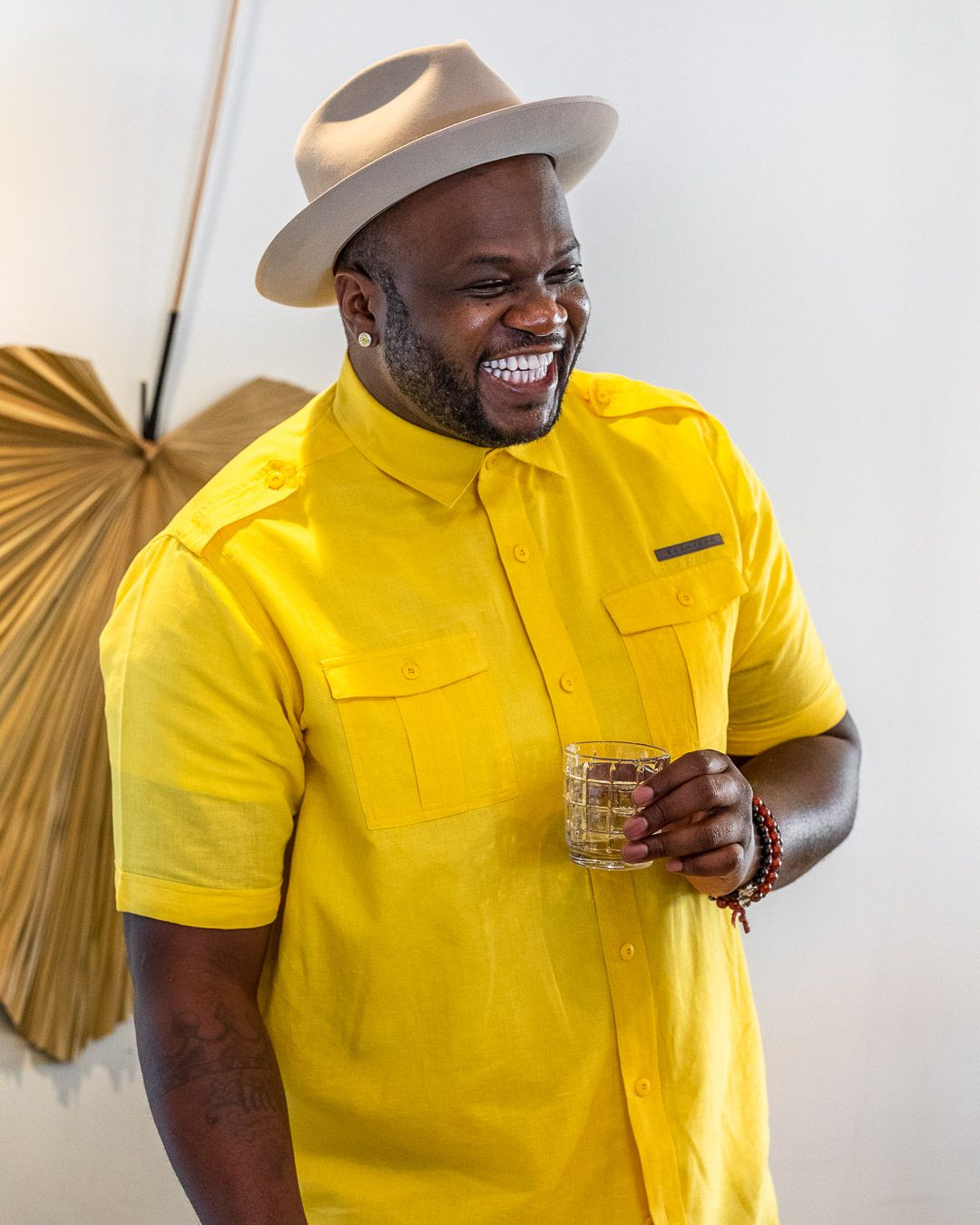 A black man wearing a bright yellow button down shirt and a tan hat while holding a glass.