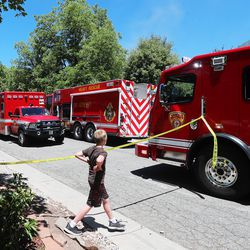 A young boy looks at the trucks as Unified Fire Authority firefighters fight a fire at 3381 S. 3170 East in Millcreek on Sunday, July 5, 2020.