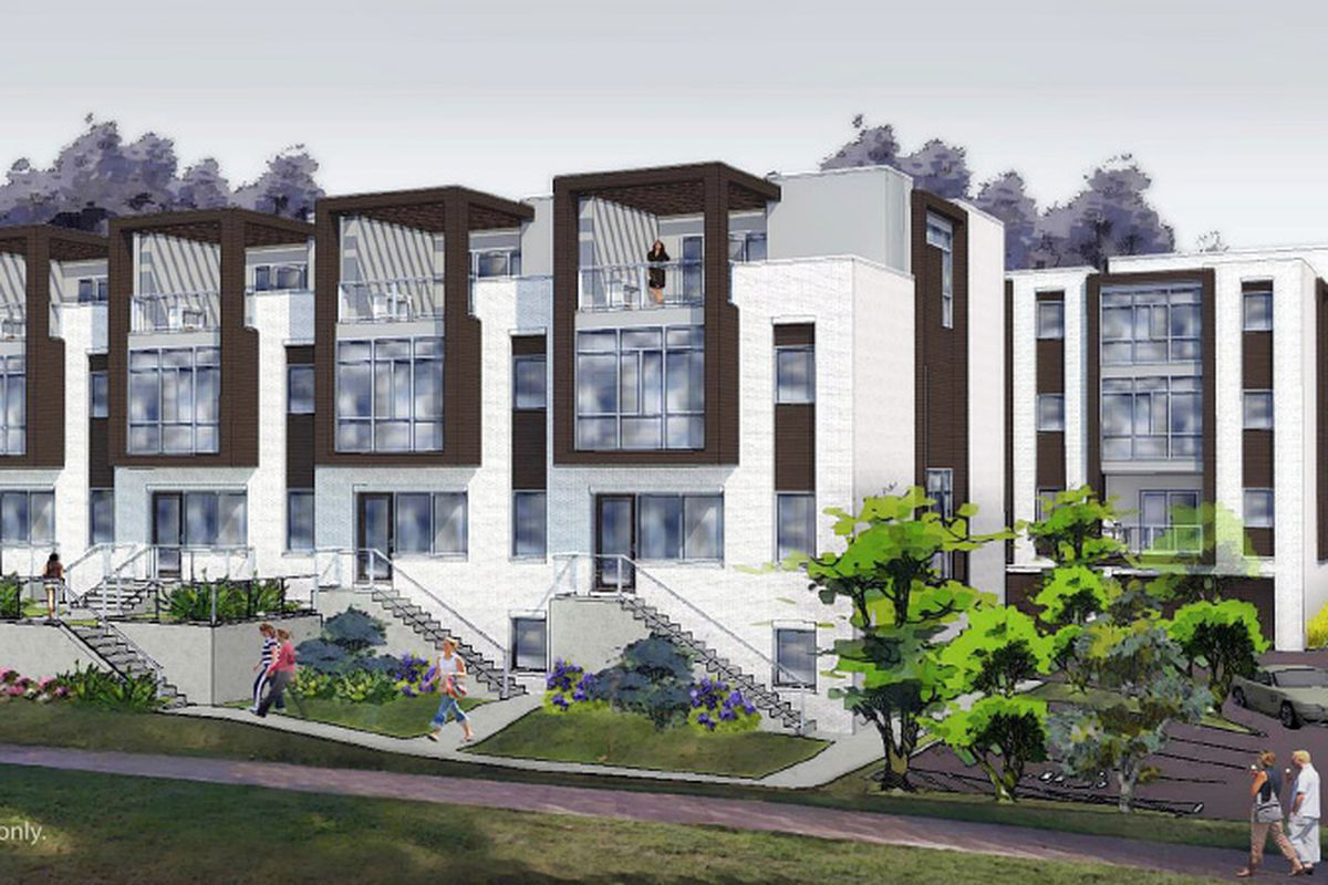Minimalist townhomes, painted white, with two-story glass walls and balconies.