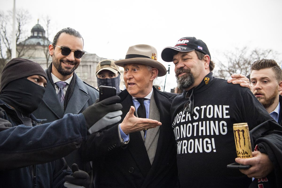 """Roger Stone stands outside the Supreme Court beside a man wearing a shirt that reads """"Roger Stone did nothing wrong!"""""""