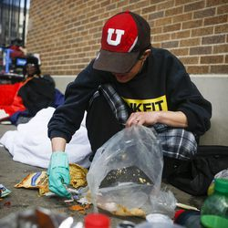 """Criss, left, cleans the area around where she stays outside the Catholic Community Services (200 S. and 500 W.) next to the Road Home, called """"The Block,"""" in Salt Lake City on Wednesday, March 8, 2017. Chris, originally from Ohio, has been exited from the Road Home until March 12 and has relapsed since being removed from the shelter."""