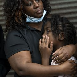 Latoya Smith, sister of Verndell Smith, comforts her daughter Zahana Hogan, 7, during a press conference at Ultimate Threat Dance Organization's studio, Thursday, May 20, 2021. Verndell, the founder of the dance studio was shot and killed yesterday.