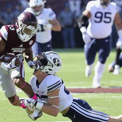 Mississippi State wide receiver Keith Mixon (23) knocks the helmet off Brigham Young defensive back Zayne Anderson (23) during the first half of an NCAA college football game in Starkville, Miss., Saturday, Oct. 14, 2017. MSU won 35-10.