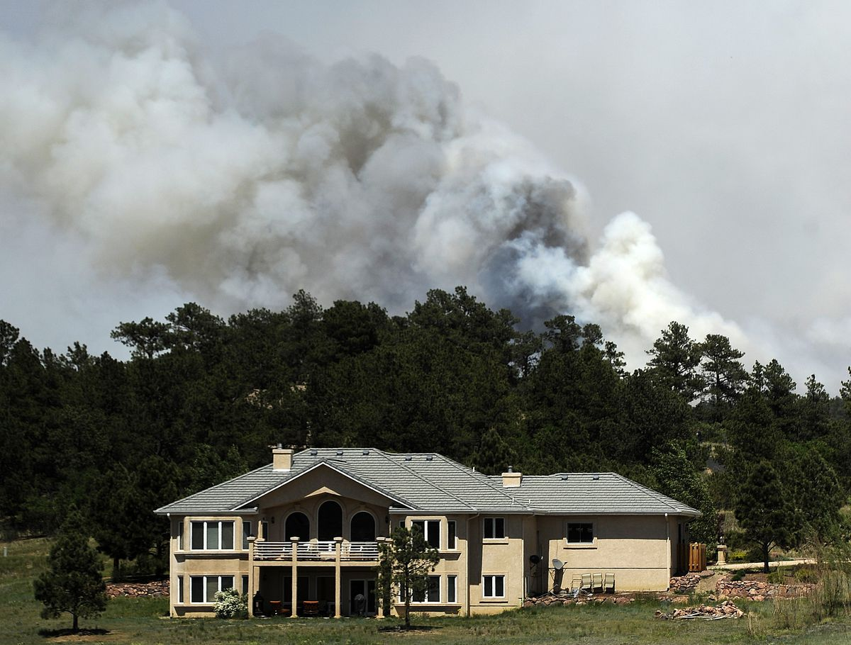 Smoke billows near a home from the Black Forest Fire on June 12, 2013 north of Colorado Springs, Colorado. (Chris Schneider/Getty Images)