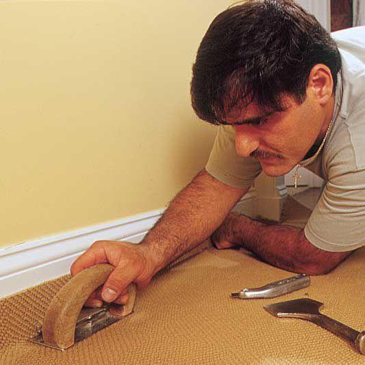 Man Uses Carpet-Edging Tool To Trim Carpet Flush With Baseboard Molding