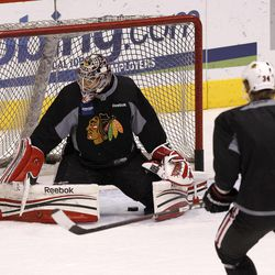 Chicago Blackhawks' Corey Crawford, left, makes a save on a shot as teammate Dylan Olsen (34) looks on during practice on Wednesday, April 11, 2012, in Glendale, Ariz. The Blackhawks and the Phoenix Coyotes are scheduled to play Game 1 of an NHL hockey Western Conference quarterfinal series on Thursday.