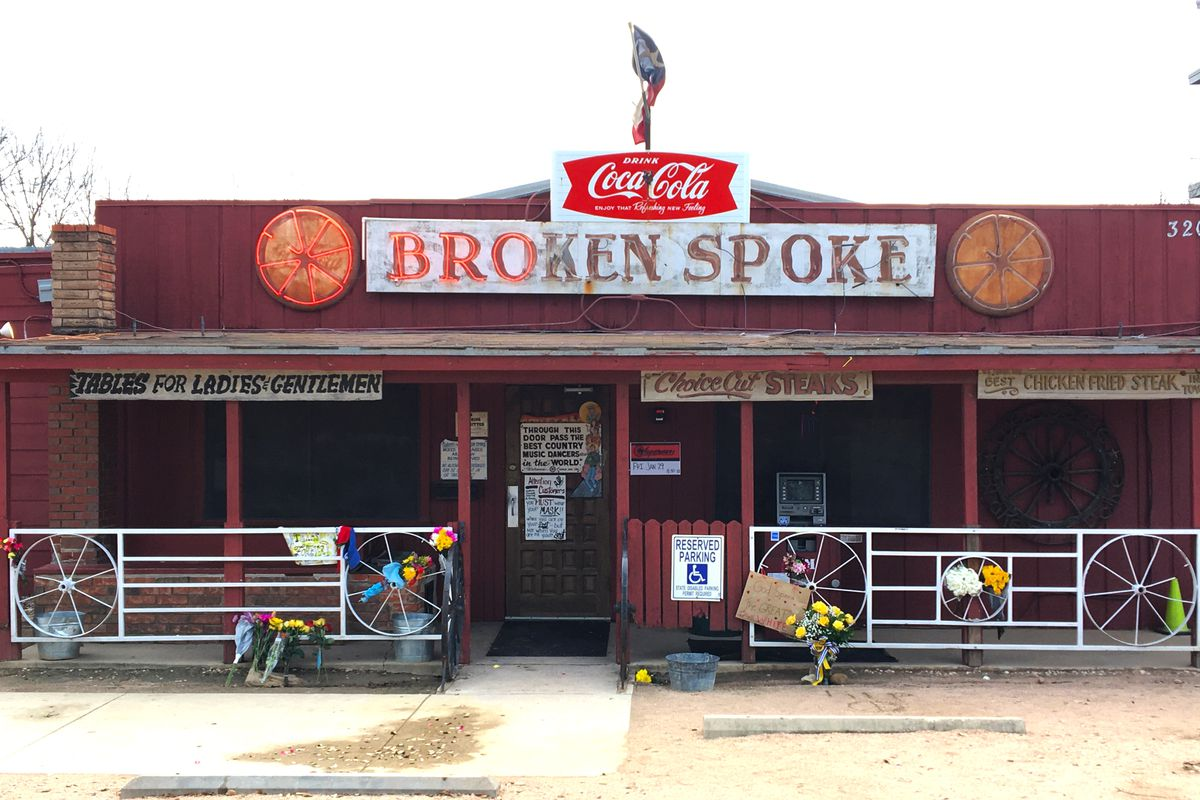 Flowers and messages of remembrance line the patio of the Broken Spoke