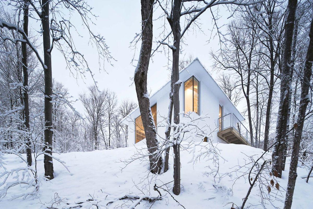 Looking up toward a white cabin in snowy landscape.