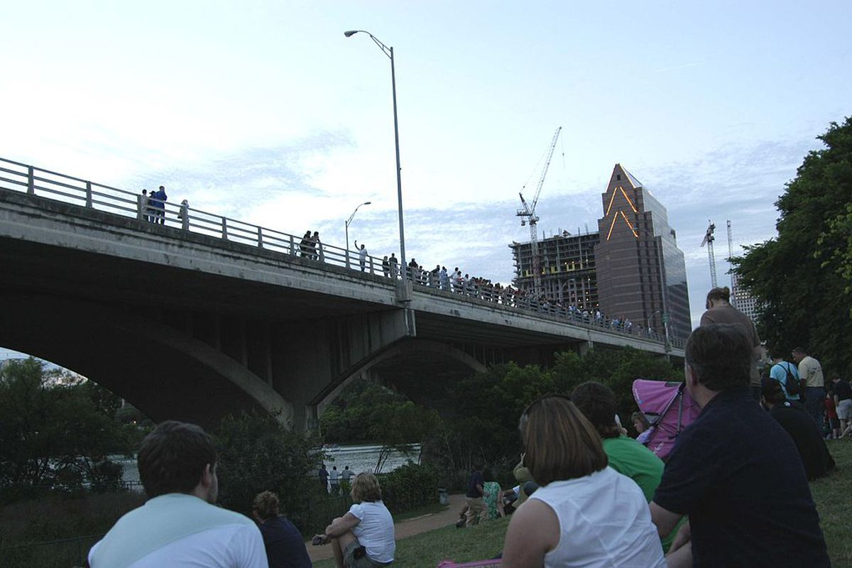 people sitting by a river, looking up at a bridge