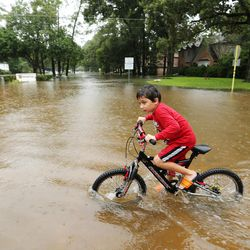 Timur Polyanctsev rides his bike in the water during Tropical Storm Harvey in Houston on Tuesday, Aug. 29, 2017.