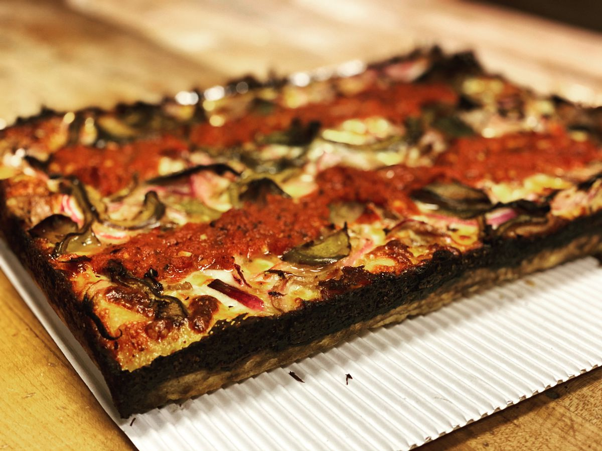 A rectangular Detroit-style pizza with a charred crust sits on white corrugated cardboard on a wooden table.