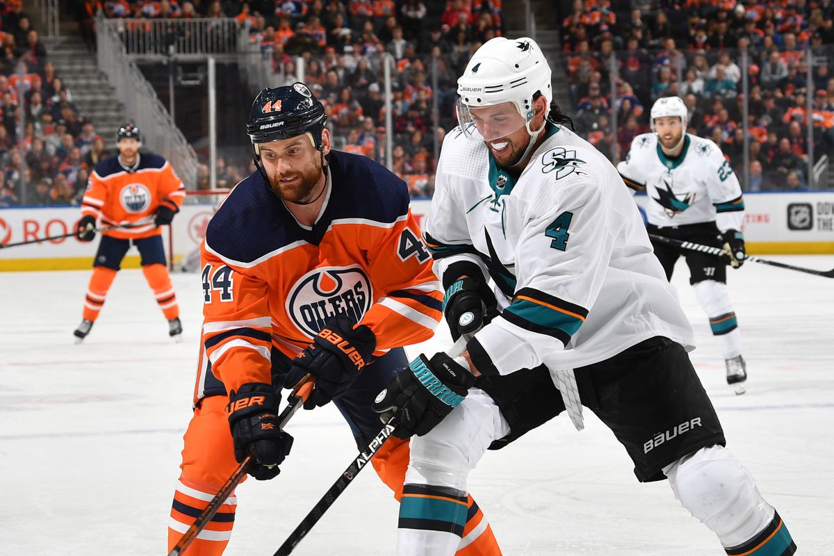 Zack Kassian #44 of the Edmonton Oilers battles for the puck against Brenden Dillon #4 of the San Jose Sharks on February 6, 2020, at Rogers Place in Edmonton, Alberta, Canada.