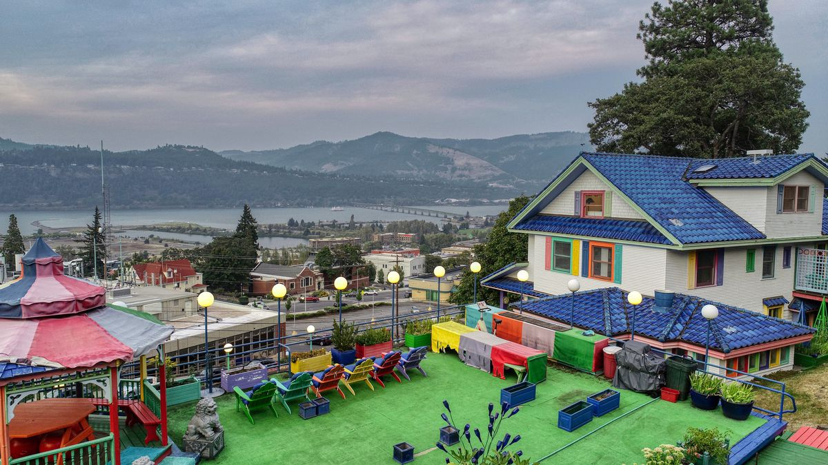 A white house with blue roof has a large patio with green astroturf, colorful lawn chairs, a gazebo, and views of the river.