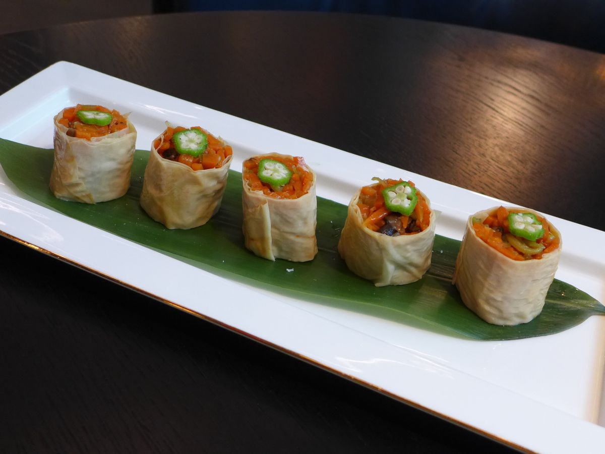 Maki type rolls made of tofu skin on a long white plate lined up with vegetables inside.