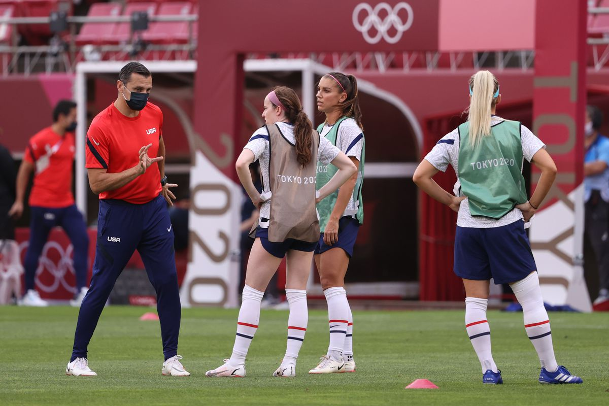 Vlatko Andonovski, Head Coach of Team United States speaks with Rose Lavelle #16 and Alex Morgan #13 of Team United States during the warm up prior to the Women's Football Group G match between United States and Australia on day four of the Tokyo 2020 Olympic Games at Kashima Stadium on July 27, 2021 in Kashima, Ibaraki, Japan.