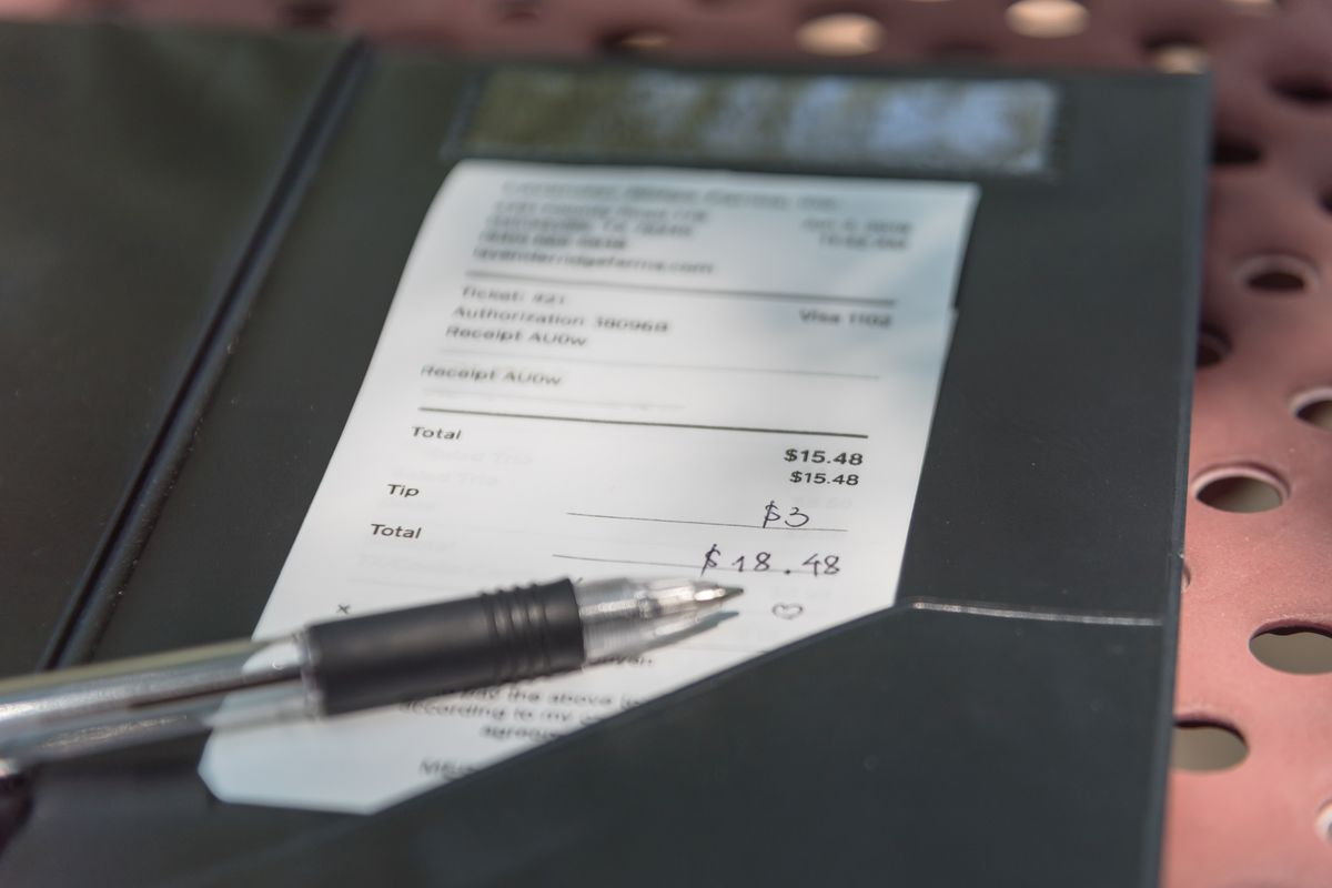 A restaurant check sits in a black booklet with a pen placed on top