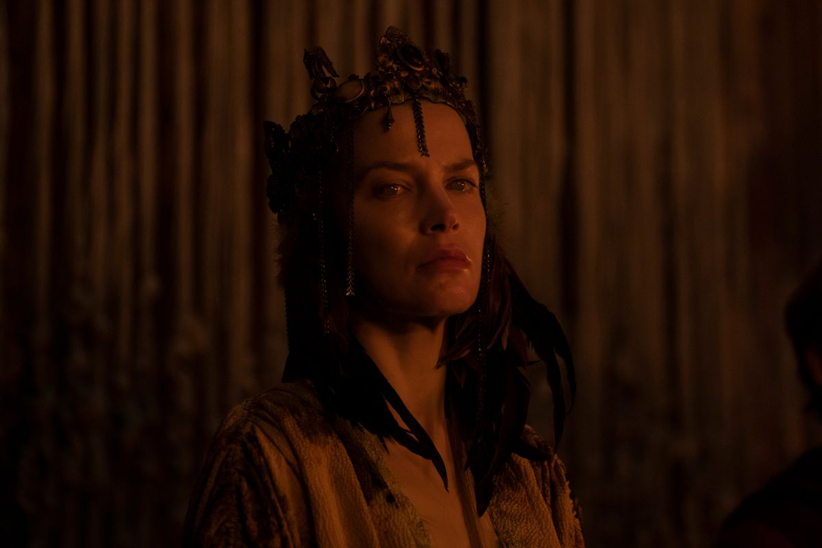 Queen Kane wears a grown as red light bathes her