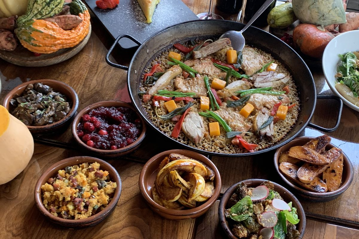 A large dish filled with turkey paella sits on a wooden table with six smaller dishes filled with various sides surrounding it