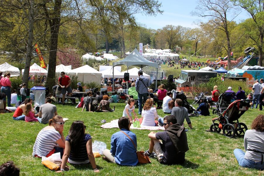 People sitting on a large lawn with vendor tents set up in the background.