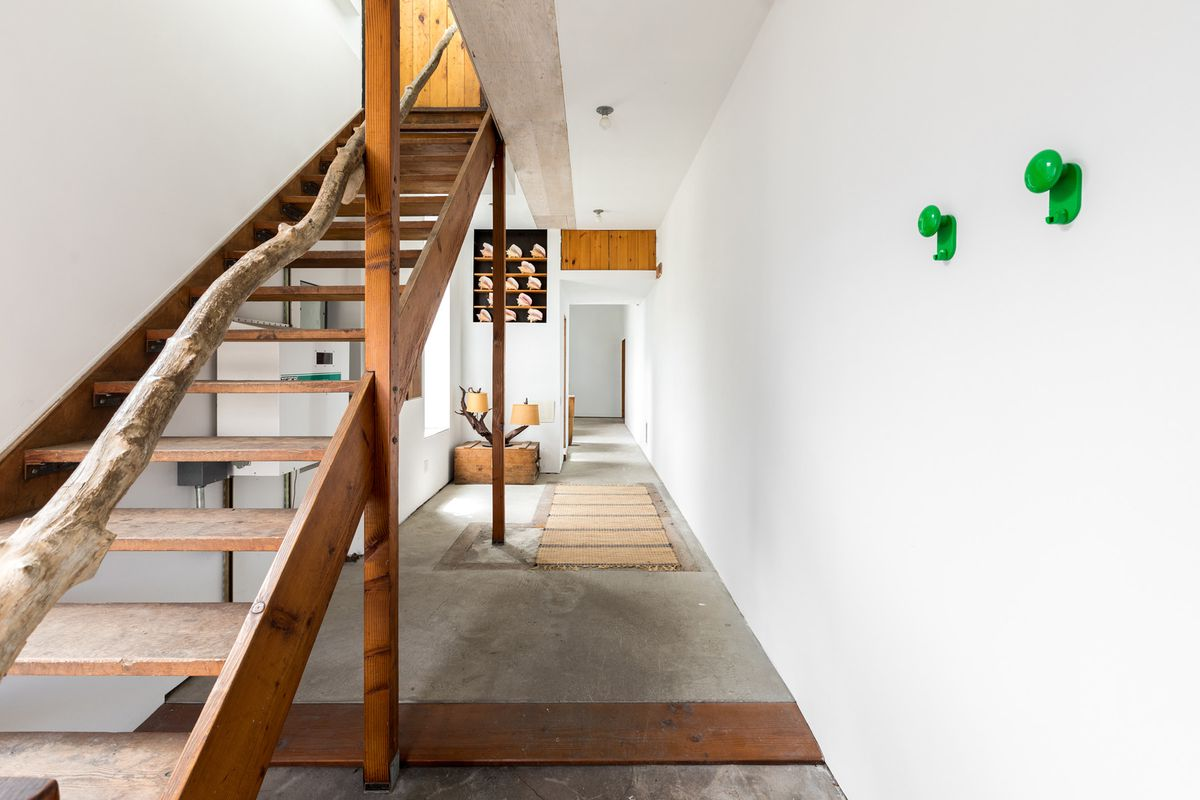 A long white hallway has wood accents and then wooden stairs leading up to a second story.