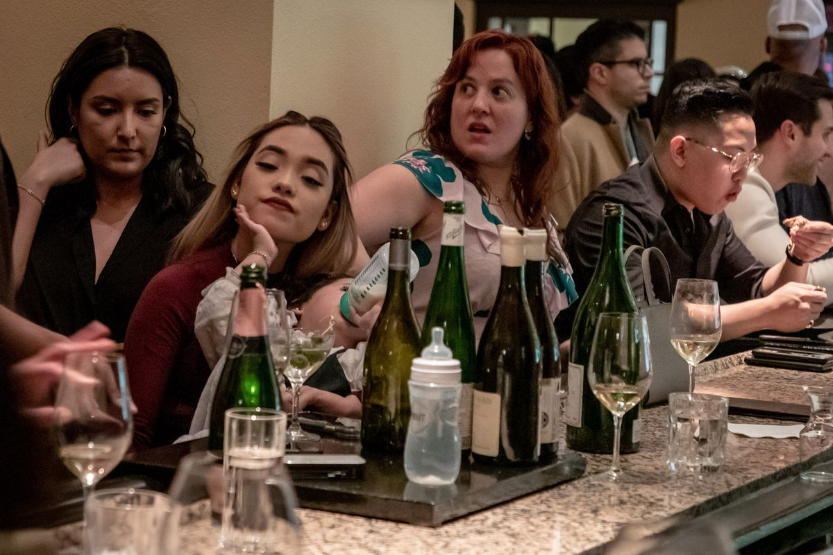 People crowd a bar that is lined with several wine bottles and an empty baby bottle. A woman also feeds a baby with a bottle.