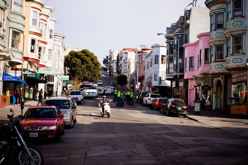 A street in San Francisco lined with various colorful houses.