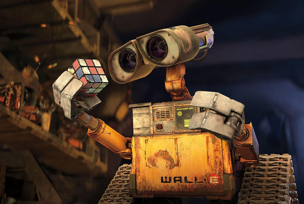 Wall-E, a robot from the film with the same name. He has a head with two eyes. His hand is holding a rubix cube toy.