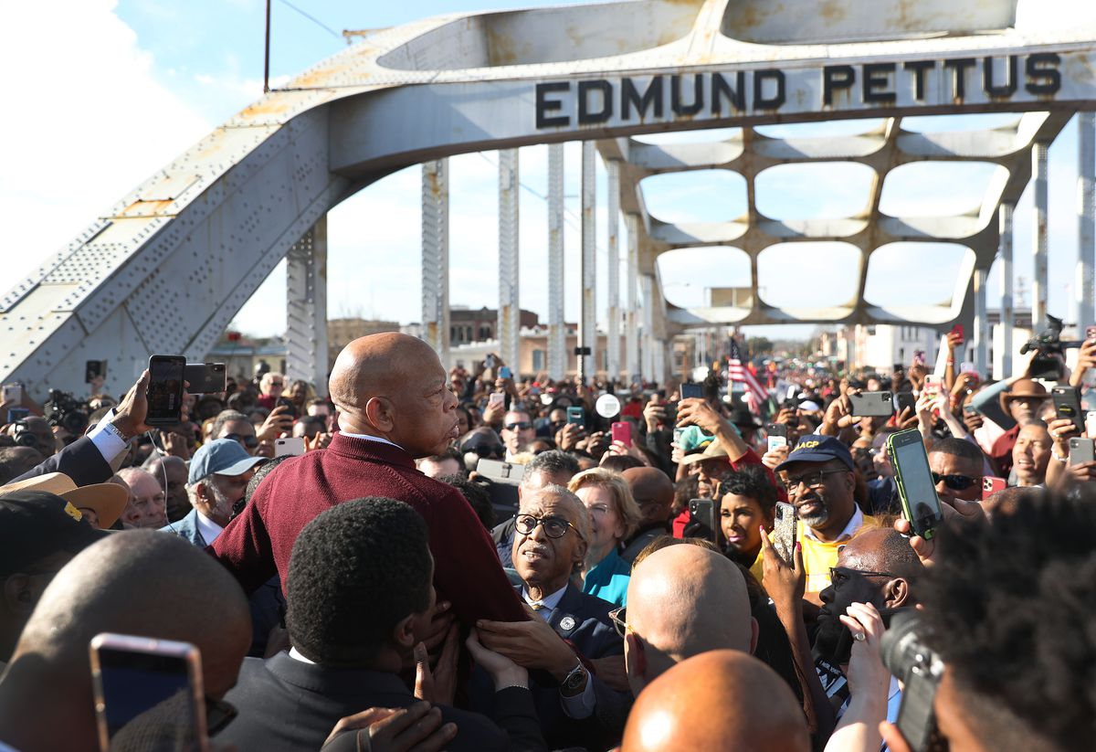 Lewis, is a red sweater, is raised above a crowd packing the Edmund Pettus Bridge. Many raise cellphones to capture the moment. Lewis looks to his right, his face grave.