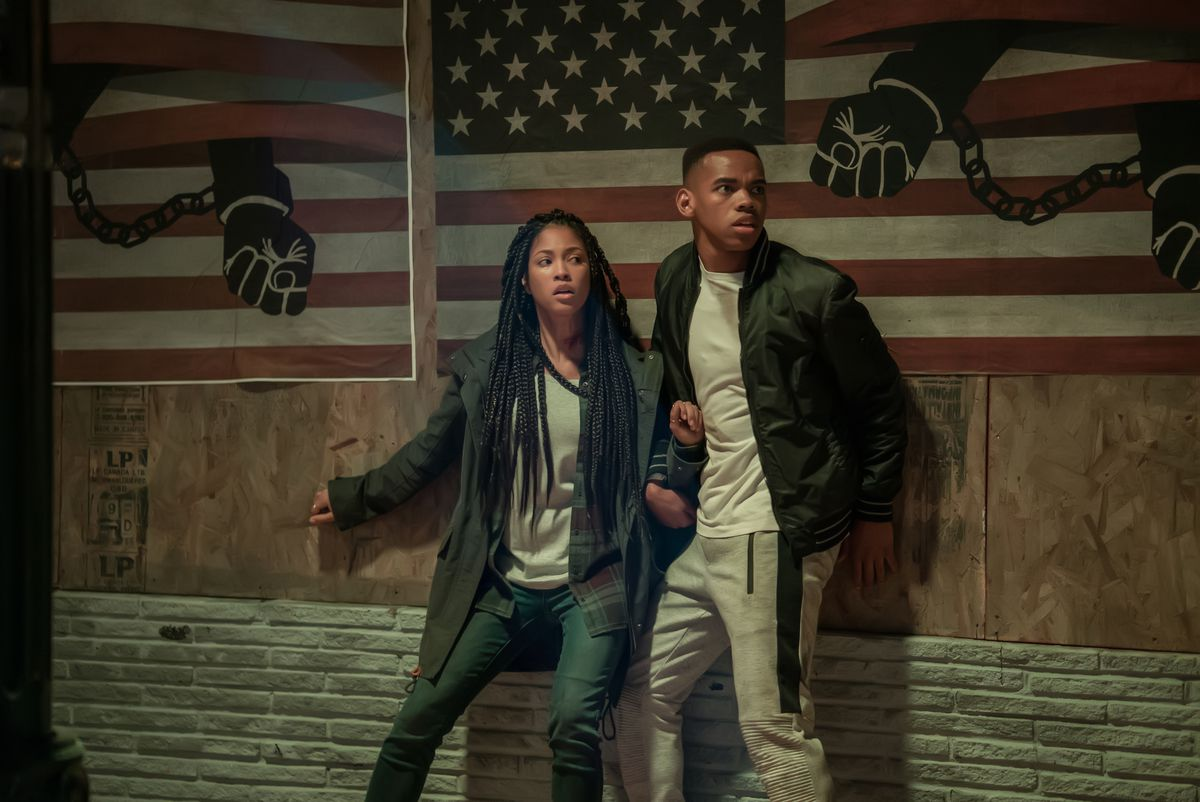 Nya (LEX SCOTT DAVIS) and Isaiah (JOIVAN WADE) stand in front of chained up arms and the american flag in the first purge