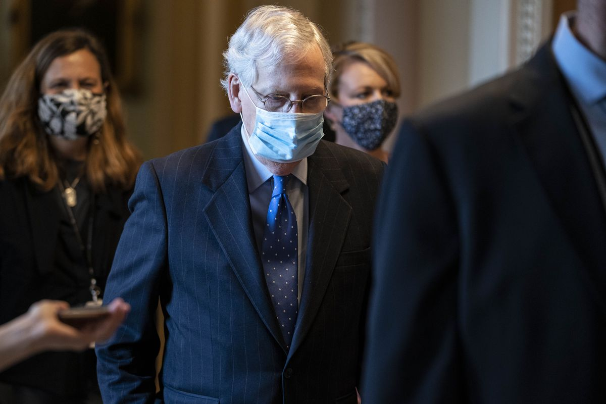 Mitch McConnell walking, wearing a mask while surrounded by others.