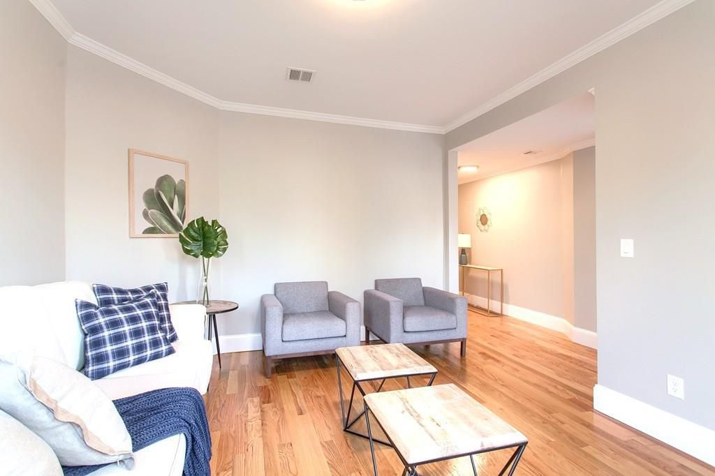 A bright living room with furniture, and there's a large opening leading off the living room.