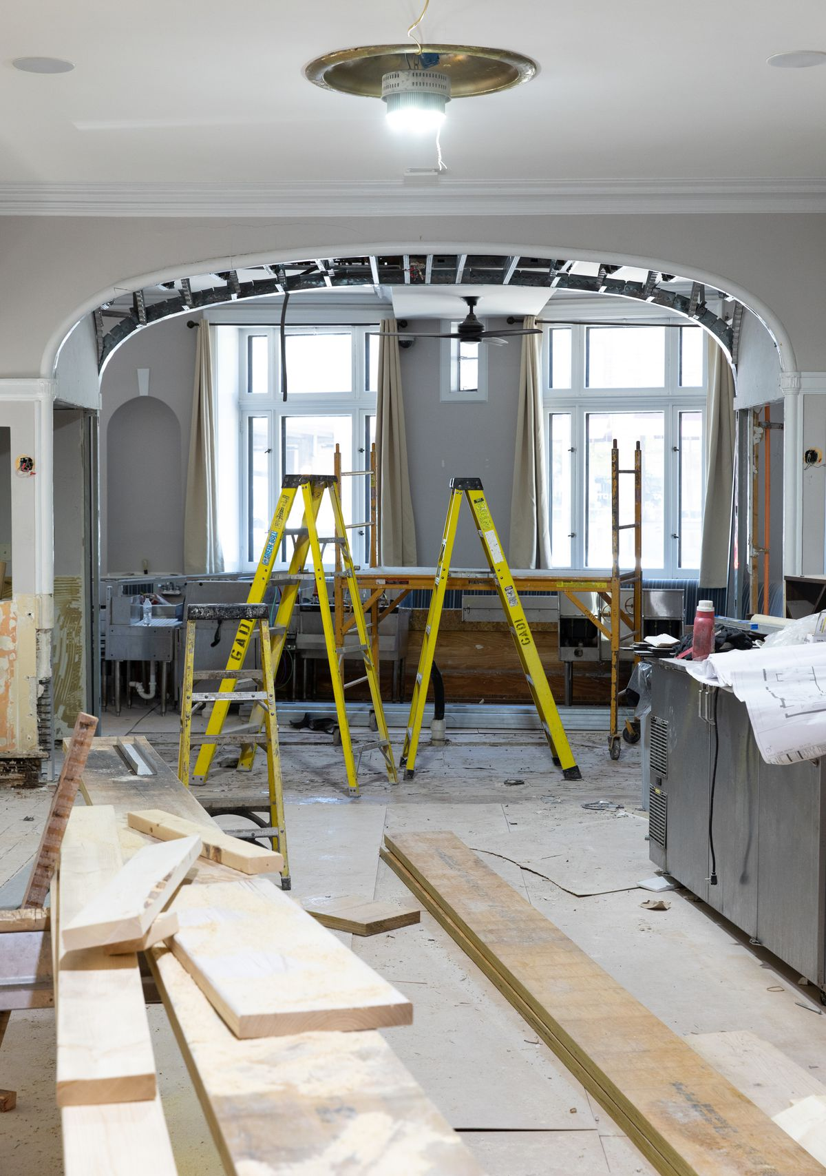 An under-construction room with exposed drywall has two bright yellow ladders in the center. An exposed arch leads to a street view.