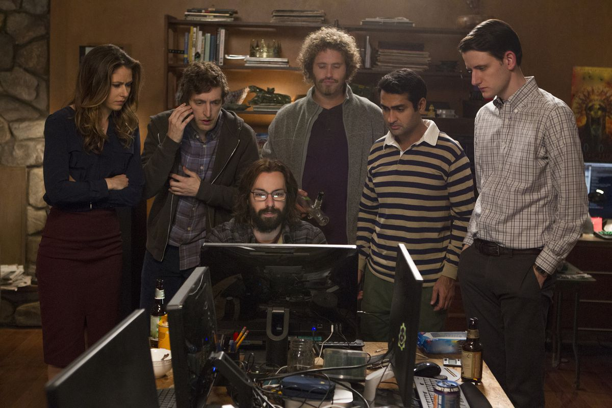 """The cast of HBO's """"Silicon Valley"""" stands and looks at a computer screen."""