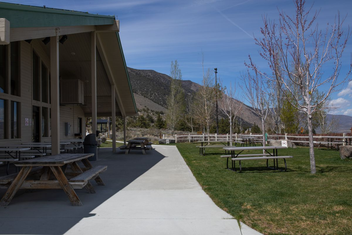 the exterior of an a-frame building with picnic tables on grass.